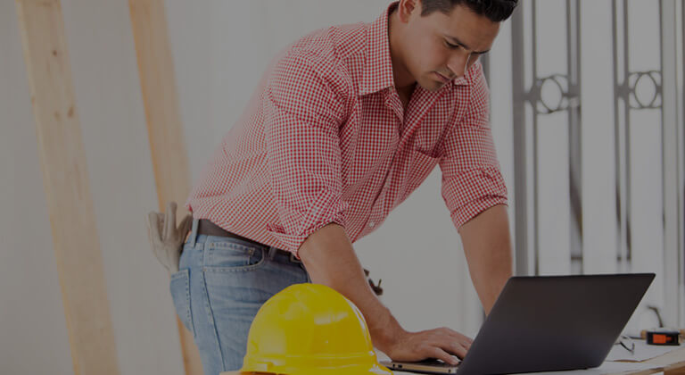 A construction worker using a laptop