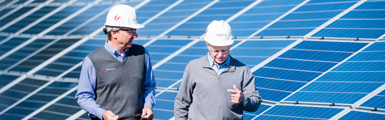 Two xcel engineers in front of solar panels