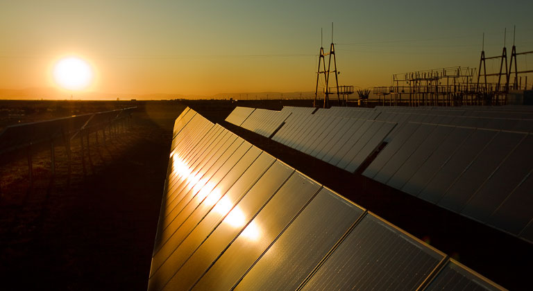 Field of solar panels at sunset