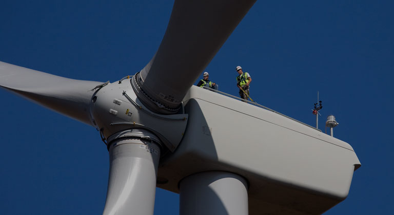 Two Xcel employees working on a windmill