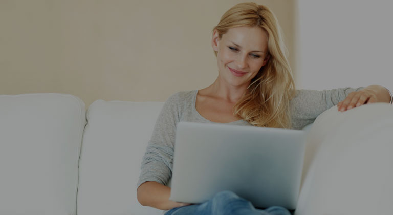 Woman using laptop on a couch