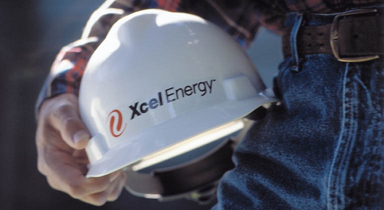 Zoomed in view of Xcel Energy employee's hard hat in hand