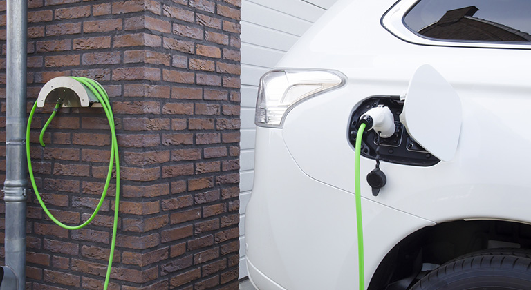 A photo of an electric car being charged at a home.
