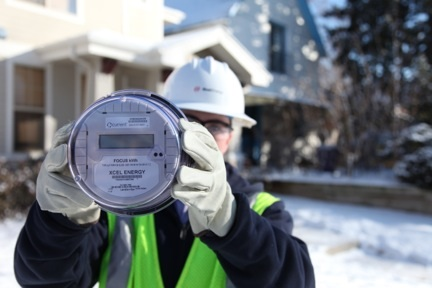 Xcel employee holding up a natural gas meter