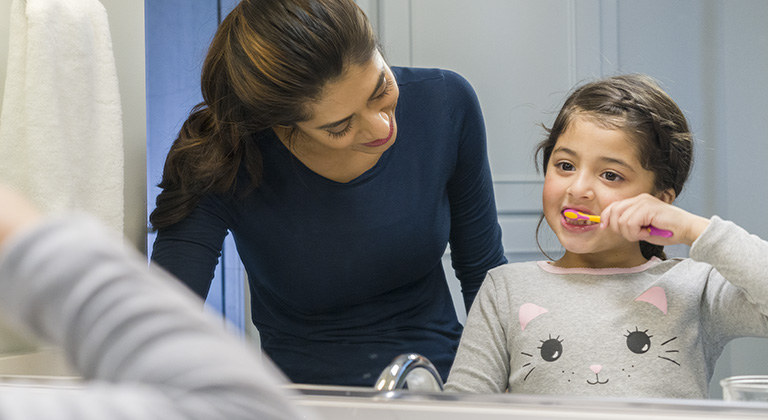 A woman watching a child brush her teeth