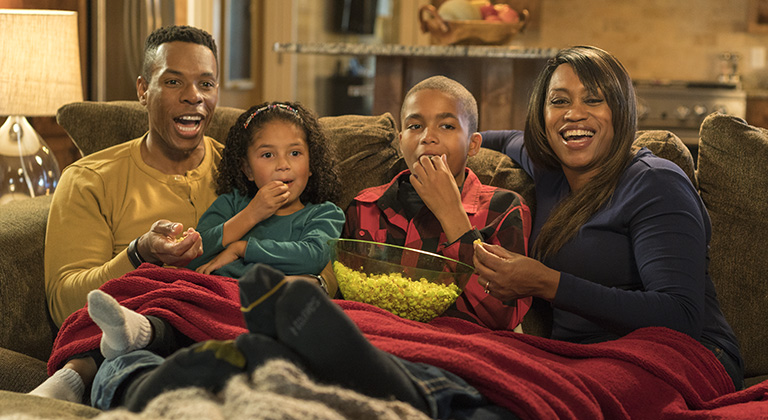 A family eating popcorn and watching a movie