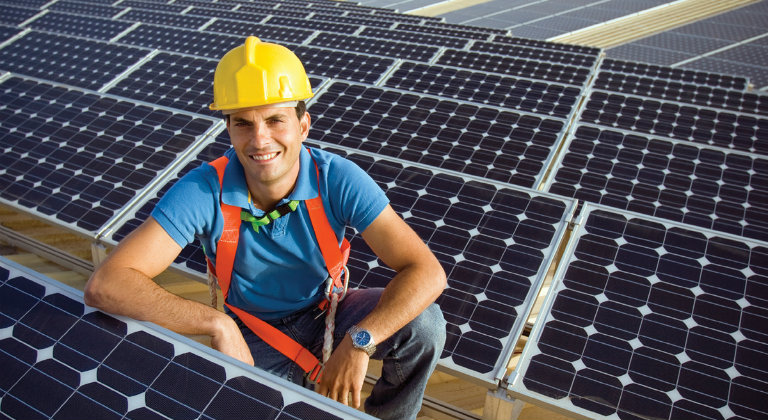 Xcel employee posing with solar panels