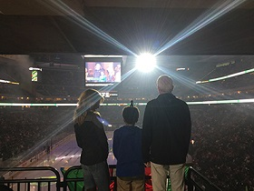 A photo of Xcel Energy CEO and president Ben Fowke and his wife Kathleen with a child at a Minnesota Wild hockey game